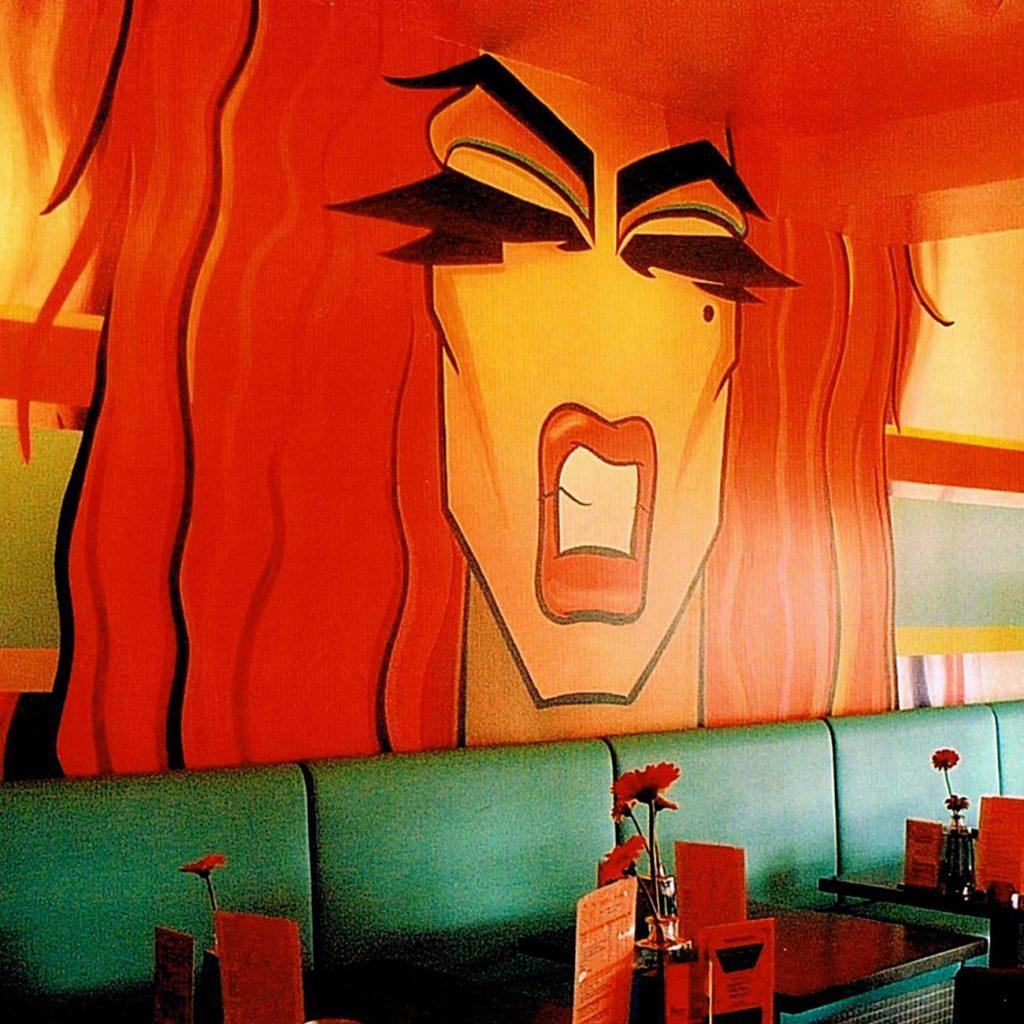 groot hoofd van vrouw met wild rood haar boven een groene bank in een café