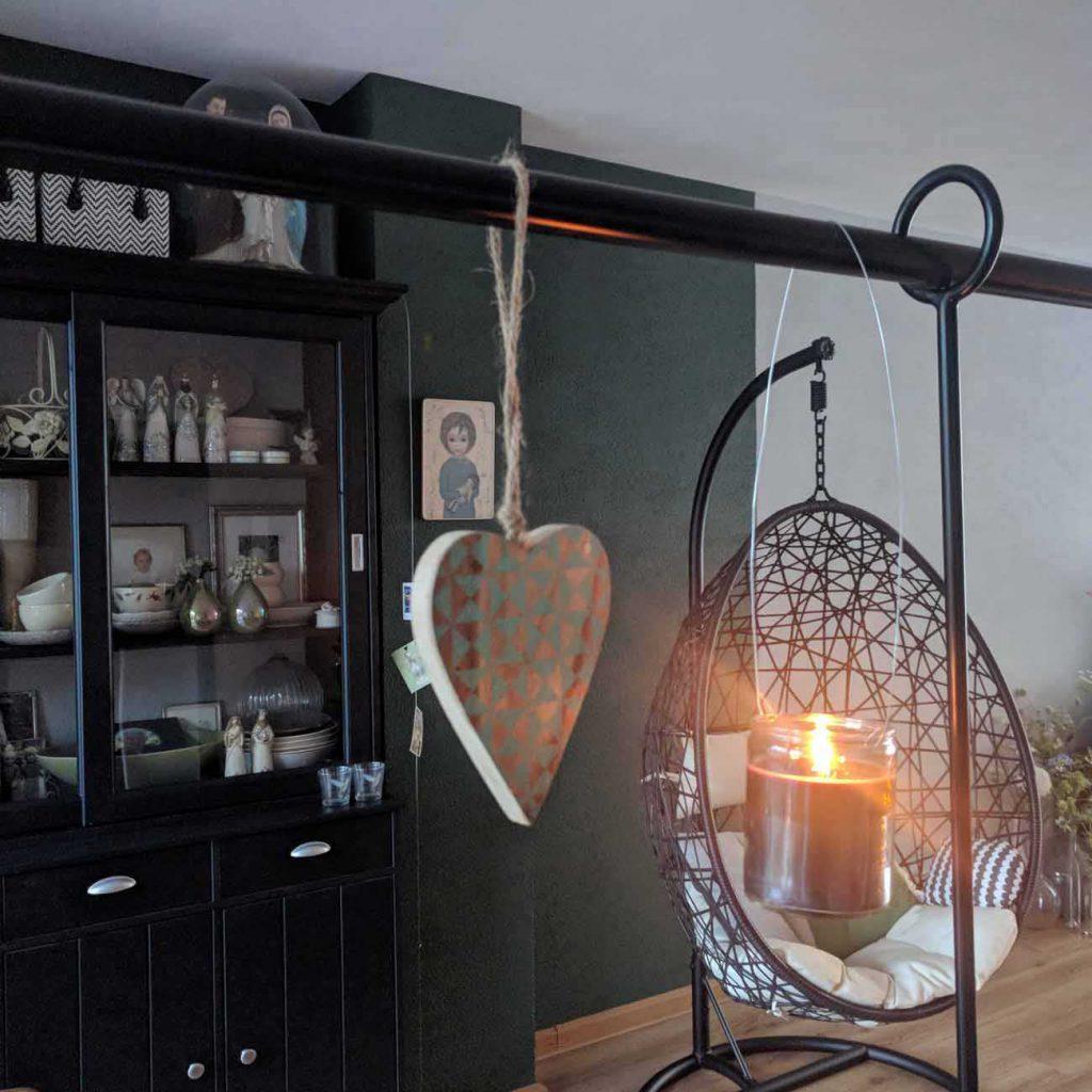 wwonkamer met een groene muur en zwarte kasten en een ei stoel