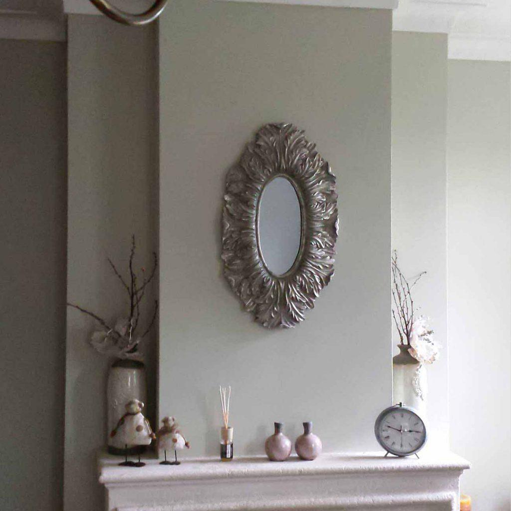 muur boven een schouw in groentint met een ovalen spiegel in het midden